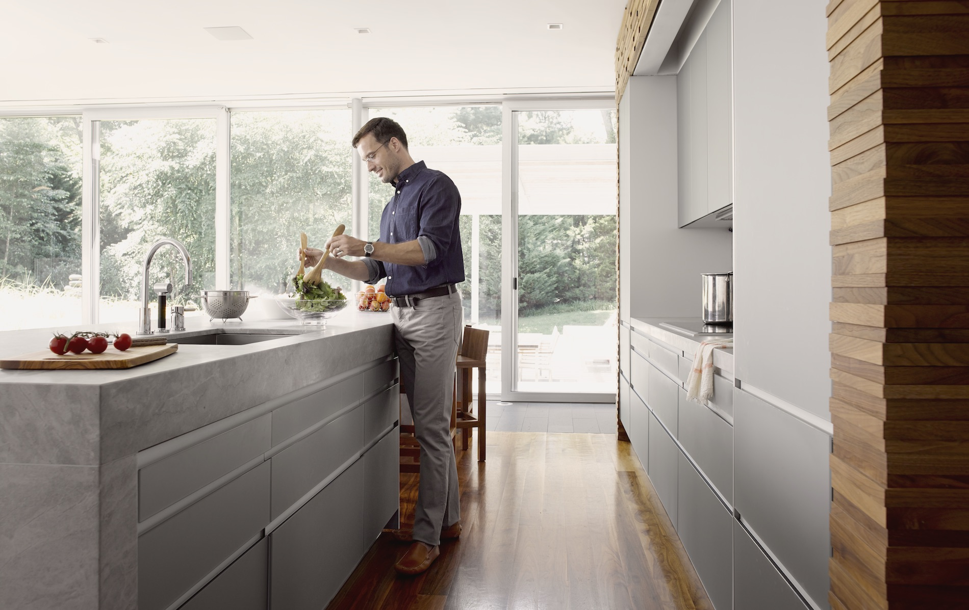 Man in modern kitchen with Savant controls